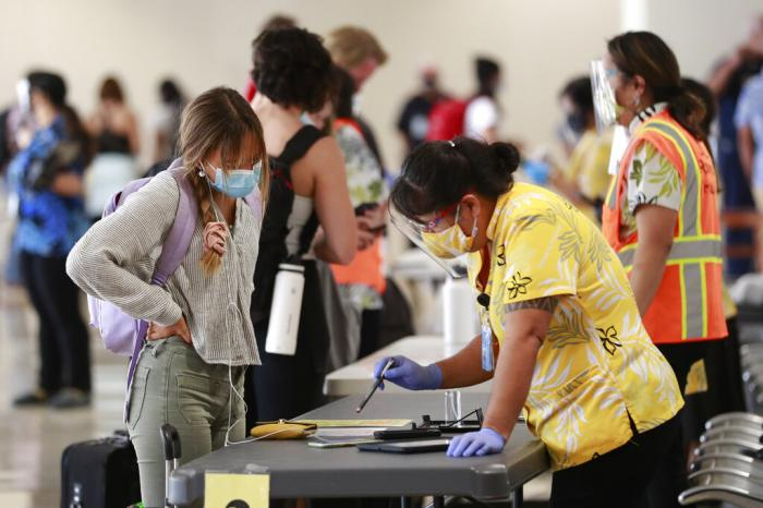 A traveler is assisted by a state official at the Daniel K. Inouye International Airport Thursday, Oct. 15, 2020, in Honolulu.