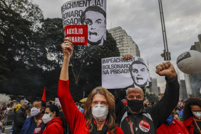 """Demonstrators hold signs that read in Portuguese; """"Impeachment now! Bolsonaro in prison"""" during a protest against Brazilian President Jair Bolsonaro and his handling of the COVID-19 pandemic, on Paulista Avenue in Sao Paulo, Brazil, Saturday, June 19, 2021"""