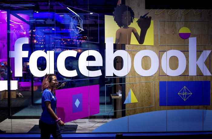 A conference worker passes a demo booth at Facebook's annual F8 developer conference, in San Jose, Calif.