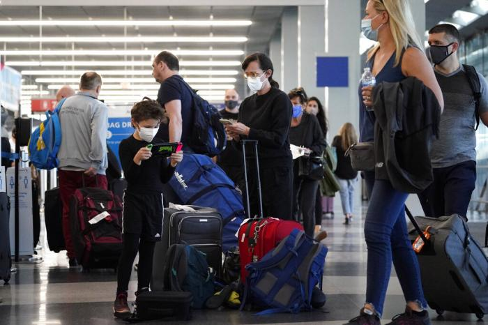 Travelers are lining up at O'Hare airport in Chicago, Friday, July 2, 2021.