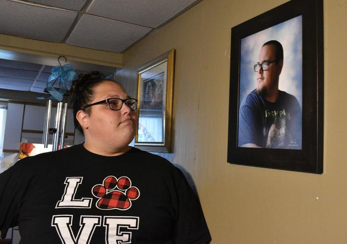 Stephanie Rimel looks at a photo of her younger brother, Kyle Dixon, inside the house he shared with his dad. Dixon, a state prison guard in rural, conservative Clearfield County, Pennsylvania, died after a battle with COVID-19.